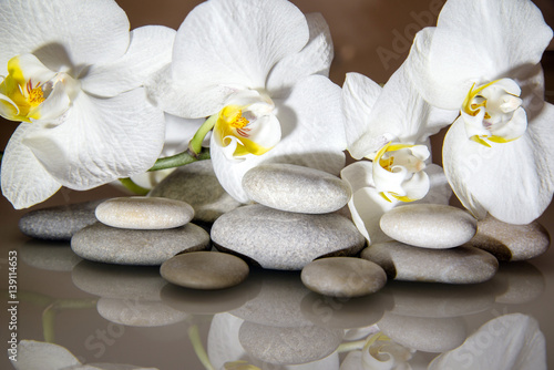 Foto op Canvas Spa flat stones on a white glass on the background of white orchids