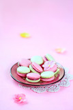 Colored (pink and green) Macarons with Raspberry Cream Filling, on pink plate, on pink background.