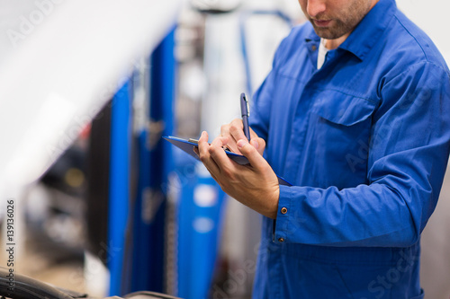 auto mechanic with clipboard at car repair shop