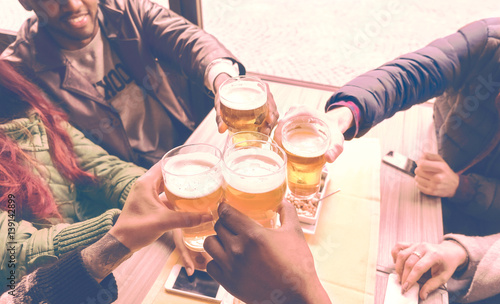 Friends Cheering With Beer Glasses Sitting Around Cafe Bar Table