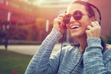 Happy young woman listening music outdoor by headphones in sunset
