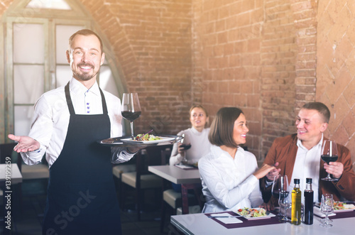 smiling man waiter demonstrating country restaurant