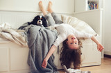 happy kid girl waking up in the morning in her bedroom with dog in bed - 139205472