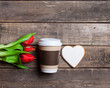 heart shaped cookie, cup of coffee and bunch of tulips lying on the wonderful brown wooden background
