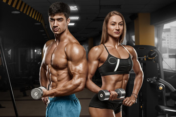 Sporty sexy couple showing muscle and workout in gym. Muscular man and wowan
