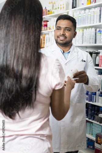 Pharmacist Giving Product To Female Customer In Pharmacy