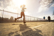 Young woman runner running on the road at morning