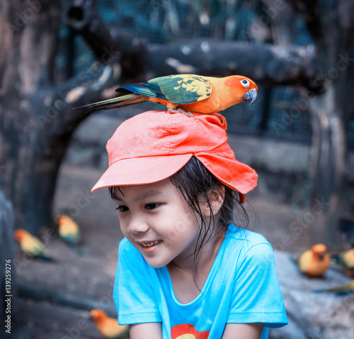 Asian girl with a colorful parrot on her head