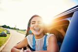 Pretty woman in speeding car smiles at camera - 139260473