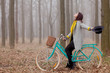 beautiful young woman sitting on the bicycle in the wonderful forest