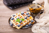 Homemade wafers with berries and coffee on a table. Selective focus. Copy space.