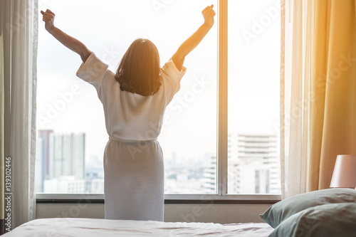 Easy lifestyle Asian woman waking up in the morning taking some rest relaxing in плакат