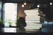 piles of books on table over blurred library background.
