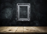silver Antique picture Frame on dark grunge wall with Wooden table top, Empty ready for product display or montage.