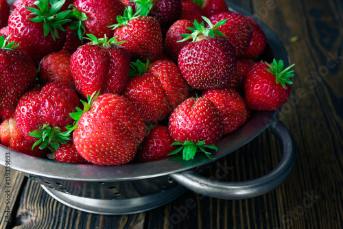 Colander with fresh strawberry on wooden background
