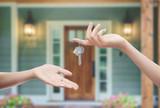 Fototapety Mani con chiavi con sfondo porta di casa