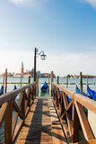 old wooden Pier and Gondolas embankment in the Grand Canal, Venice, Italy