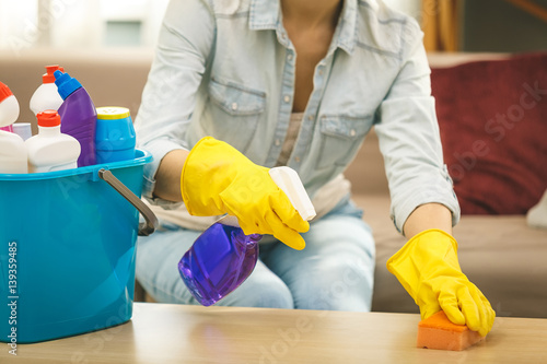 Poster Woman in protective gloves is smiling and wiping dust using a spray and a duster