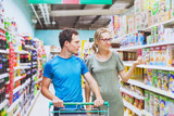 couple in supermarket, young man and woman shopping food