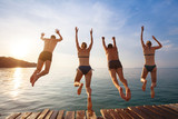 group of friends jumping to the sea from the pier, happy beach holidays - 139382423