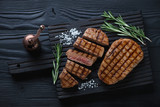 Whole and sliced barbecued beef medallions on a black wooden serving board, above view