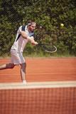Tennis player serving ball