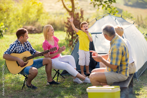 Póster child singing with family.