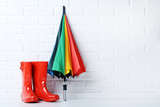 Red rubber boots with umbrella on brick wall background - 139442631