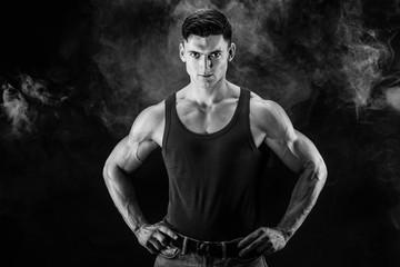 bodybuilder posing. Beautiful sporty guy male power. Fitness muscled man in shirt on dark smoky background © zamuruev