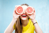 Fototapety Colorful portrait of a beautiful woman grapefruit slices on the yellow background