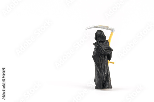 Miniature grim reaper on background with space for text