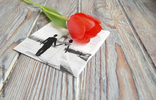 Foto Murales Красный тюльпан и салфетка с символом Парижа   лежат на деревянном столе