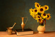 Sunflower in a ceramic vase and books on the table