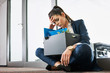 Fired young woman, employee sitting with box outside the office