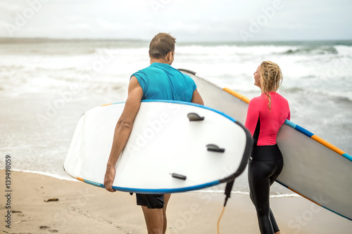 Couple of surfers on ocean's shore