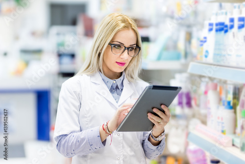 Poster Apotheek Pharmacy details - blonde doctor in white uniform using tablet and technology in pharmaceutical or medical field
