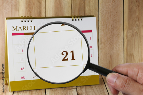 Poster Magnifying glass in hand on calendar you can look Twentieth one day of month,Focus number twenty-one in March