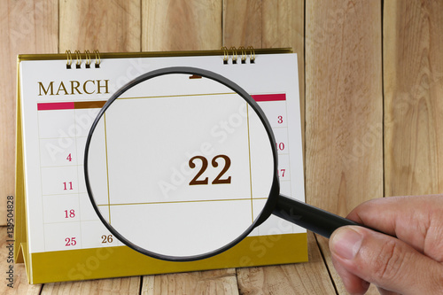 Poster Magnifying glass in hand on calendar you can look Twenty-two day of month,Focus number Twenty-two in March