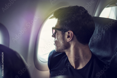 Poster Side view of handsome young man against plane window sitting and looking out