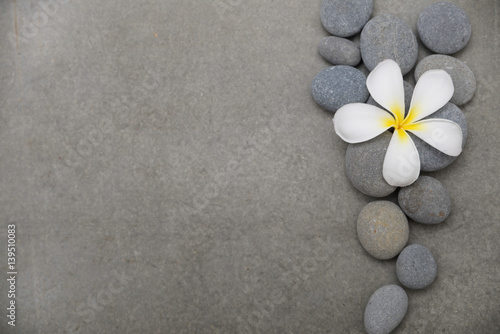 Tuinposter Spa frangipani with spa stones on grey background.