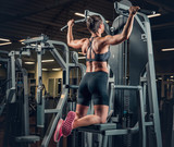 Female with short hair doing pull ups in a gym club.