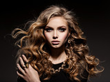 Beautiful woman with long curly hair and gold jewelry