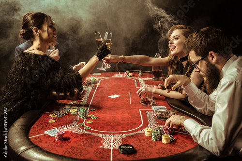 side view of women clinking drinks while playing poker in casino