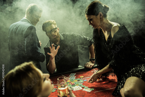 side view of group of people playing poker together in casino плакат