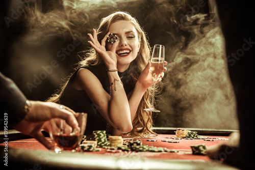 Plakat portrait of smiling woman with drink and poker chip playing poker