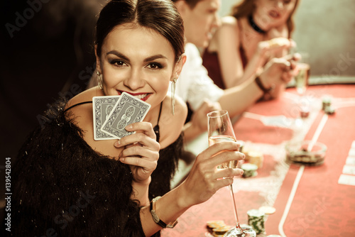 portrait of smiling woman with drink and cards playing poker плакат