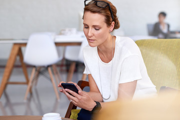 Busy woman looking at mobile phone