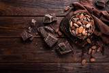 Fototapety Cocoa beans and chocolate on wooden background