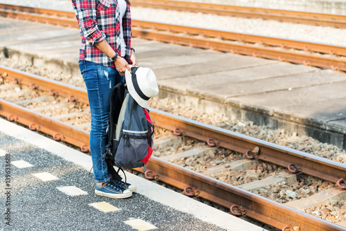 Traveler women wearing backpack holding map, waiting for a train. Poster