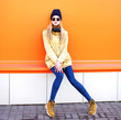 Fashion pretty blonde woman on a orange colorful background in city